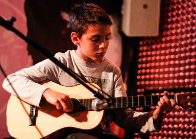niño tocando guitarra castello en mondo ritmic escola de música